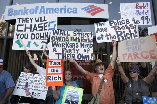 People demonstrate in front of a Bank of America as Occupy Los Angeles protesters march in Los Angeles